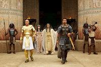 """Während Pharao Seti (John Turturro, M. r.) Adoptivsohn Moses (Christian Bale, r.) liebt und sehr schätzt, hegt seine Frau Tuya (Sigourney Weaver, M. l.) eine große Abneigung für das Kind fremder Leute. Nach dem Tod des Pharaos gelingt es ihr, ihren Sohn Ramses (Joel Edgerton, l.), den neuen Pharao, gegen seinen """"Bruder"""" aufzuwiegeln ..."""
