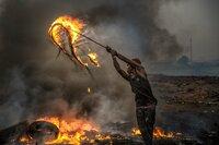 Mit Autoreifen wird das Feuer zur Verbrennung der Plastikteile angeheizt, Agbogbloshie (Ghana).