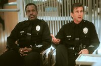 Nach einem missglückten Einsatz müssen Roger Murtaugh (Danny Glover, l.) und Martin Riggs (Mel Gibson, r,) Streifendienst leisten - und das alles wenige Tage vor Rogers Pensionierung