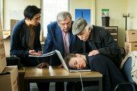 Umzugschaos: Vicky Adam (Katja Danowski) schläft erschöpft am Computer ein.  Hui Ko (Aaron Le, l), Günter Hoffmann (Wolfgang Winkler, M.) und Edwin Bremer (Tilo Prückner, r.) sorgen sich um die Chefin.