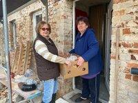 Helga Woy (l.) von der Tafel Torgau übergibt Essen an Hilfsbedürftige.