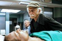 Dr. Jamm (Michael Kors, l.) ist ermordet worden. Edwin Bremer (Tilo Prückner, r.) mustert die Leiche, Kollege Günter Hoffmann (Wolfgang Winkler, im HG) hält sich im Hintergrund.