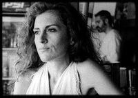 Artemis (Maria Tzivani) sitzt an der Strandbar am Tresen, während Nasos (Stavros Markalas) Getränke macht.