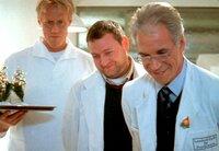 Der geltungssüchtige Leiter einer Nervenklinik Prof. Schönborn (Wolf Roth, rechts) und sein Assistent Dr. Müller (Maximilian Krückl, Mitte) feiern mit ihren Patienten Weihnachten.