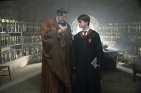 Professor Horace Slughorn (Jim Broadbent )  wearing cape and mortarboard, holding small bottle, and talking with Harry Potter. (Daniel Radcliffe)