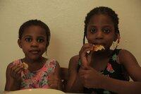 Ogechi wohnt in Berlin. In ihrem Haus ist auch ihre Kita. Dort will sie, gemeinsam mit ihrer Schwester, für ihre Freunde Kartoffelpuffer machen.