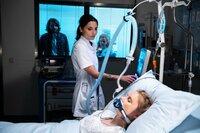 Fabian (Frederik Götz, l.) beobachtet tief besorgt, wie Dr. Leonie Mertens (Linda Marlen Runge, M.) sich um seine schwer verletzte Verlobte Emma Krämer (Franziska Breite) kümmert.