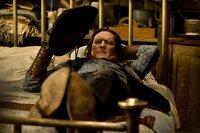 Joe _Der Cowboy_ Gage (Michael Madsen) wartet mit einigen anderen zusammen in einer Holzhütte auf das Ende des Schneesturms.