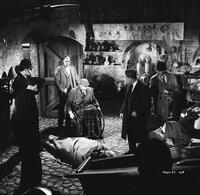 Da purzelt die Leiche aus dem Sarkophag: Inspektor Craddock (Charles 'Bud' Tingwell, hinten 2.v.r.) und Sergeant Bacon (Gordon Harris, hinten r.) entdecken in Luther Ackenthorpes (James Robertson Justice, hinten 2.v.l.) Schatzkammer einen Leichnam ...