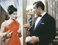James Bond (Sean Connery, r.) hat nicht nur Glück im Spiel, sondern auch bei Frauen. Die bezaubernde Sylvia Trench (Eunice Gayson, l.) hängt sofort an seinen Lippen.
