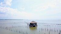 Über Jahrhunderte zog es die Menschen an die Küsten, wo sie ihre Siedlungen bauten. Aber was, wenn dem Meer nicht mehr zu trauen ist? Wie hoch werden die Ozeane infolge des Klimawandels ansteigen?; Letztes Haus einer Ortschaft, das sich gegen den Rückzug vor dem Wasser wehrt in Indonesien.