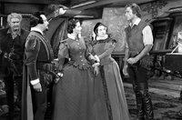 Kapitän Thorpe (Errol Flynn, re.) und seine Mannschaft plündern eine spanische Galeasse. Es ist das Schiff des Botschafters Don José (Claude Rains, 2.v.l.), der seine Nichte Doña Maria (Brenda Marshall, Mi.) an den Hof von Königin Elisabeth bringen möchte.