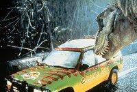 Ein Tyrannosaurus Rex ist aus dem Sicherheitsareal ausgebrochen und naehert sich einen Wagen, in dem zwei Besucher sitzen.