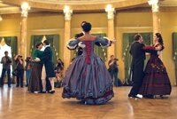 Pair in historical clothes dancing a waltz in a ballroom