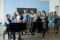 Voller Elan und mit hartem Umgangston probt der Musiklehrer Nickel (Tom Gerhardt, l.) mit dem Chor, um perfekt für die Abschlussfeier gerüstet zu sein ...