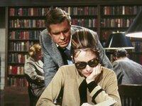 Der verkrachte Schriftsteller Paul Varjak (George Peppard) besucht Holly Golightly (Audrey Hepburn) in der Stadtbibliothek, wo sie sich über das Land ihres künftigen Millionärsgatten informiert.