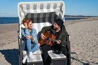Johannes Oerding spielt Moderatorin Laura Dahm während des Interviews am Strand einen Song auf der Gitarre vor.