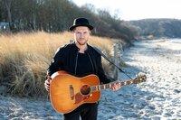 Johannes Oerding steht am Strand mit seiner Gitarre.
