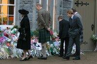 Die Queen (Helen Mirren, l.) ist aus dem schottischen Balmoral nach London zurückgekehrt. Mit ihrem Mann Prinz Phillip (James Cromwell, m.), den Prinzen William (Jake Taylor Shantos, vorne r.), Harry (Dash Barber, 2.v.r.) und Charles (Alex Jennigs, fast verdeckt r.) sieht sie sich die Blumen an, die die Menschen an den Buckingham Palace gebracht  haben, um an die tote Diana zu erinnern.