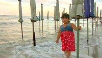 """Thailändische Touristen kommen am ganz frühen Morgen oder am späten Nachmittag kurz vor Dämmerung zum Strand. Sie gehen angezogen ins Wasser und """"spielen im Meer"""", wie hier das kleine Mädchen."""