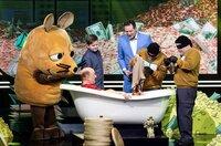 Carl-Justus (l) möchte wissen: Wie viele Ein-Cent-Münzen passen in eine Badewanne? Während Eckart von Hirschhausen (3.v.l.) mitzählt, wie viele Münz-Säcke von den Helfern in die Wanne geschüttet werden, nimmt Comedian Bernhard Hoëcker (l) ein Bad.