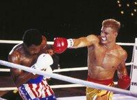 """Der von Rocky trainierte Apollo Creed (Carl Weathers, li.) tritt gegen die """"sibirische Kampfmaschine"""" Ivan Drago (Dolph Lundgren) an. Doch bereits in der ersten Runde wirkt Creed schwer angeschlagen..."""