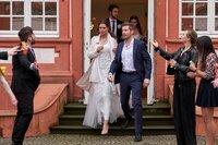 Alex Rode (Jan Hartmann) und Laura Seifert (Susan Hoecke) kommen aus dem Gebäude gelaufen und werden für das Brautpaar gehalten.
