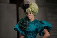 Katniss' und Peetas Betreuerin ist Effie Trinket (Elizabth Banks). Sie trägt immer eine Perücke in einer knalligen Farbe und dazu passendes Makeup ...