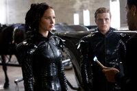 Dank des ausgefallenen Stylings von Cinna (Lenny Kravitz, r.) gelingt es Katniss (Jennifer Lawrence, l.) und Peeta (Josh Hutcherson, M.), schon in der Präsentationsshow das Publikum für sich zu gewinnen. Aber reicht dies auch für einen Sieg aus?