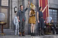 """Auch Effie (Elizabeth Banks, M.) kann ihre """"Zöglinge"""" Katniss (Jennifer Lawrence, r.) und Peeta (Josh Hutcherson, l.) nicht davon abhalten, deutliche Zeichen zu setzen. Deshalb beschließt Präsident Snow, die beiden dauerhaft und endgültig aus dem Verkehr zu ziehen ..."""