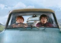 """Obwohl urplötzlich ein Hauself bei Harry (Daniel Radcliffe, r.) erscheint, um ihn vor einer Verschwörung zu warnen und davon abzuhalten, zu Hogwarts zurückzukehren, macht er sich gemeinsam mit seinem Freund Ron (Rupert Grint, l.) im einem """"geliehenen"""" Auto zur Zauberschule auf ..."""