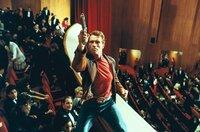 """Das Publikum staunt nicht schlecht: Bei der Premiere des neuen """"Jack-Slater""""-Films erscheint der Star (Arnold Schwarzenegger, m.) höchst selbst und jagt einen Verbrecher."""
