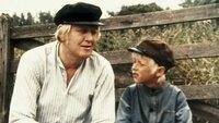 Alfred (Björn Gustafsson) und Michel (Jan Ohlsson) sitzen auf der Bank und beobachten, wie Lina mit einem fremden Bauern flirtet.