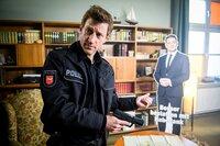 Henk Cassens (Maxim Mehmet) staunt nicht schlecht, als er einen Pappaufsteller von Habedank im Mohnschen Bestattungsinstitut findet.