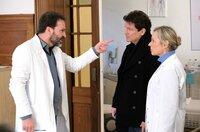 Dr. Dietrich Frahm (Mathias Herrmann, l.) attackiert im Beisein seiner Frau Barbara Frahm (Jana Hora-Goosmann, r.) Dr. Christian Kleist (Francis Fulton-Smith, M.). Er hat ihn nach angeblichen Behandlungsfehlern gefragt.