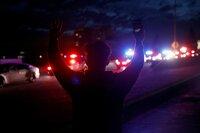 Während einer Demonstration gegen Polizeigewalt und den Tod George Floyds hebt ein Demonstrant angesichts einer Fahrzeugkolonne der California Highway Patrol in Oakland die Arme.