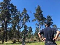 Ein Helikopter mit dem sogenannten Bambi-Bucket, einem Wassertransportbehälter, im Anflug zum Testabwurf. Christoph Lamers vom Institut der Feuerwehr in NRW beobachtet die Übung aus sicherer Entfernung.