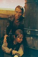 Nicht nur Danny (Austin O`Brien, unten), sondern auch die Film-Bösewichte landen in der realen Welt. Nun muss auch der Film-Cop Jack Slater (Arnold Schwarzenegger, hinten) den Sprung in die Wirklichkeit wagen ...