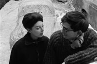 Christo und Jeanne-Claude jung und verliebt vor einem verhüllten Fahrzeug, fotografiert von Charles Wilp