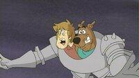 Scooby-Doo (re.) und Shaggy besuchen einen Jahrmarkt mit Ritterspielen. Plötzlich taucht ein Drache auf, der dem Vergnügen ein jähes Ende bereitet.