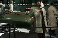 Der aus Deutschland emigrierte Wissenschaftler Abraham Erskine (Stanley Tucci, r.) macht aus dem schmächtigen Soldaten Steve Rogers (Chris Evans, liegend) mit Hilfe eines von ihm entwickelten revolutionären Serums einen mit unglaublichen Kräften ausgestatteten Supersoldaten ...