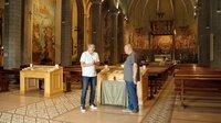 """Joachim Llambi (l.) zusammen mit dem Pfarrer von Blanes (r.) auf den Spuren seiner Vorfahren in der """"Iglesia de Santa Maria de Blanes_."""
