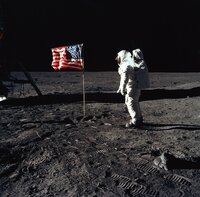 Astronaut Buzz Aldrin bei seinen ersten Schritten auf dem Mond. Neben ihm eine animierte USA Flagge.