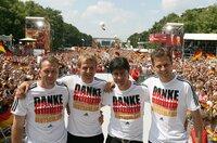 Torwart-Trainer Andreas Koepke (l-r), der damalige Bundestrainer Jürgen Klinsmann, sein damaliger Co-Trainer Joachim Löw und Team-Manager Oliver Bierhoff stehen auf der Fan-Meile am Brandenburger Tor zusammen.