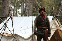 Oliver standing in front of wall tent.
