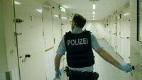 Polizeikommissar Adi schaut in den Zellentrakt der Wache, weil ein Mann in Gewahrsam genommen werden soll.