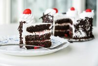 Detail on a Slice of a Black forest cake, or traditional austria schwarzwald cake from dark chocolate and sour cherries on wooden table