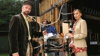 """Lothar Frettner (Wolf Hofer, l.) präsentiert der Journalistin (Christiane Scheda) seine selbst konstruierte """"Lärmrückwurfmaschine"""", mit der er seinen Nachbarn endlich das Singen abgewöhnen will..."""