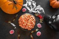 Halloween Brain mini cake, Pumpkins and Halloween Decor on dark background, top view, copy space. Homemade dessert idea for Halloween.