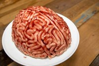 A cake in the shape of a brain with strawberry source brushed on it to make the sponge cake look like a real human bloody brain for the halloween party food desert